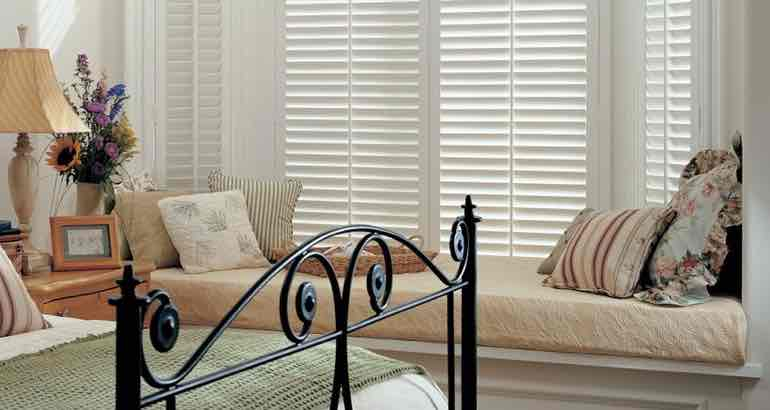White shutters in a chic bedroom bay window.