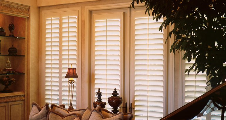 Plantation shutters on windows and door in New Brunswick parlor