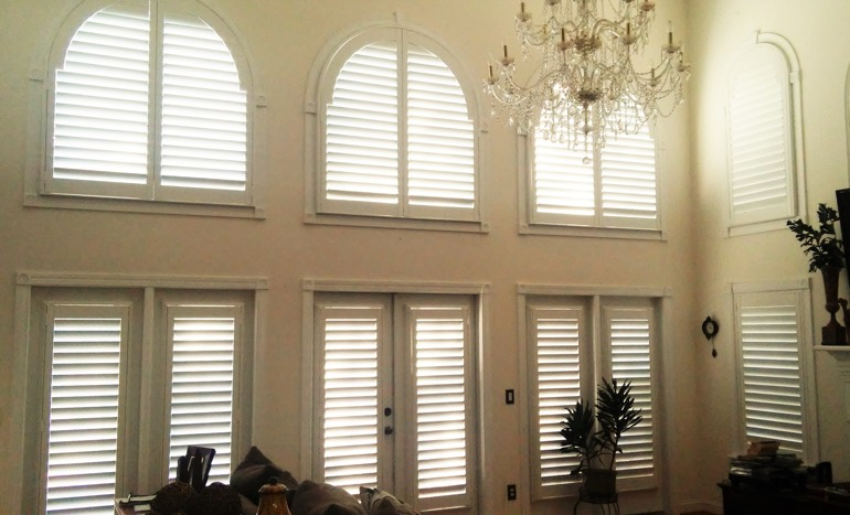 Great room in two-story New Brunswick home with plantation shutters on high ceiling windows.