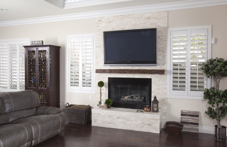 White plantation shutters in a New Brunswick living room with dark hardwood floors.