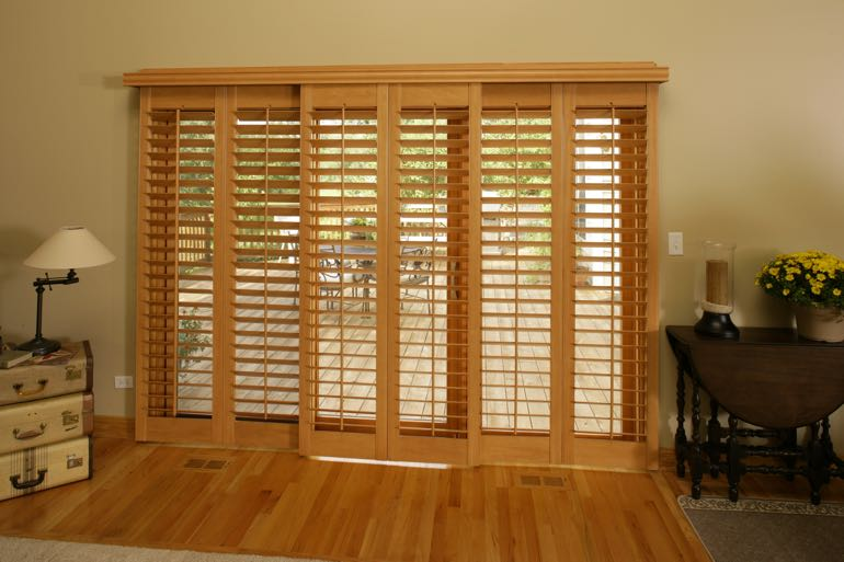 plantation shutters on sliding door leading to full porch.